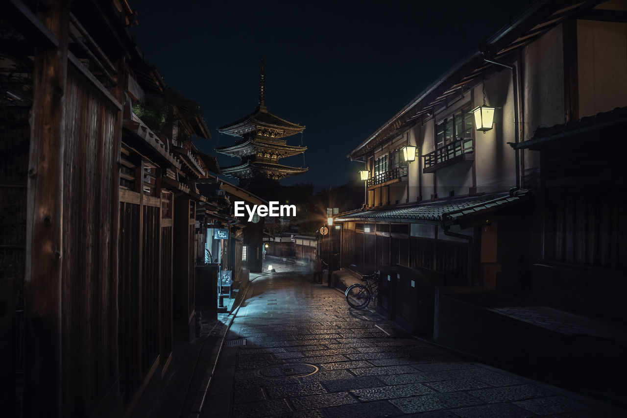 Empty illuminated alley amidst buildings at night