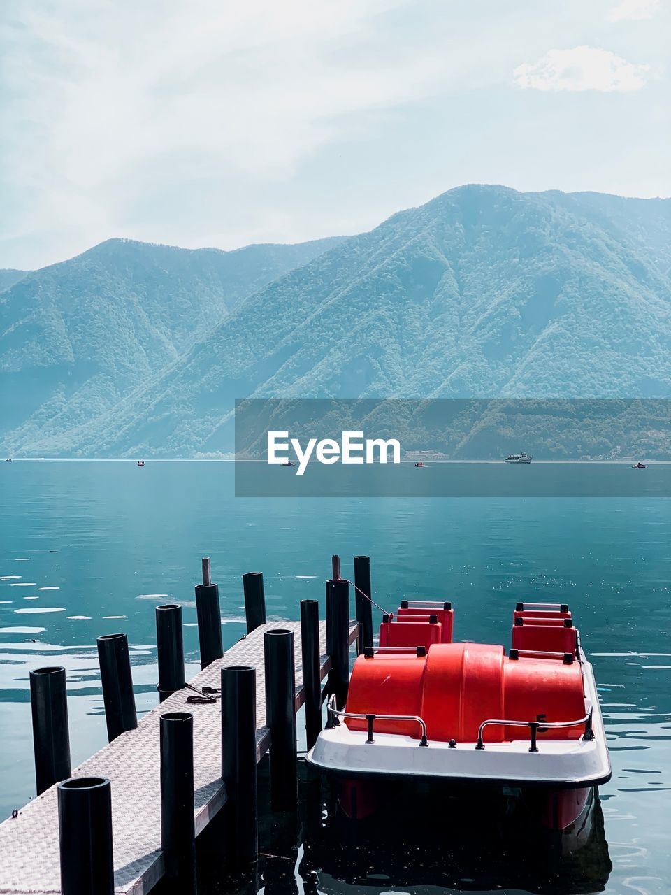 mountain, water, beauty in nature, scenics - nature, sky, nautical vessel, day, mountain range, nature, tranquil scene, red, no people, tranquility, transportation, non-urban scene, lake, idyllic, mode of transportation, outdoors, inflatable, snowcapped mountain