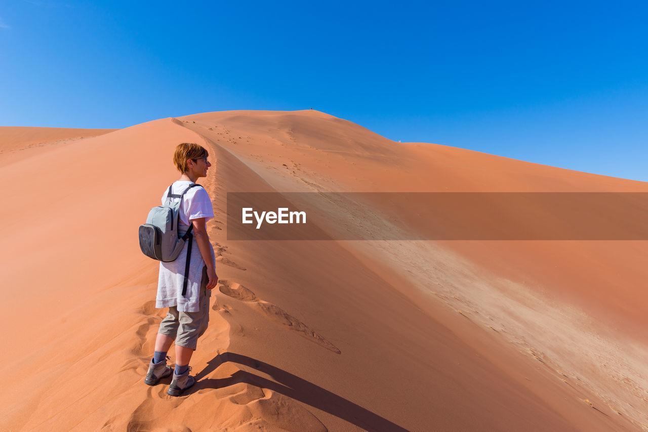 Full length of woman standing on desert against clear blue sky