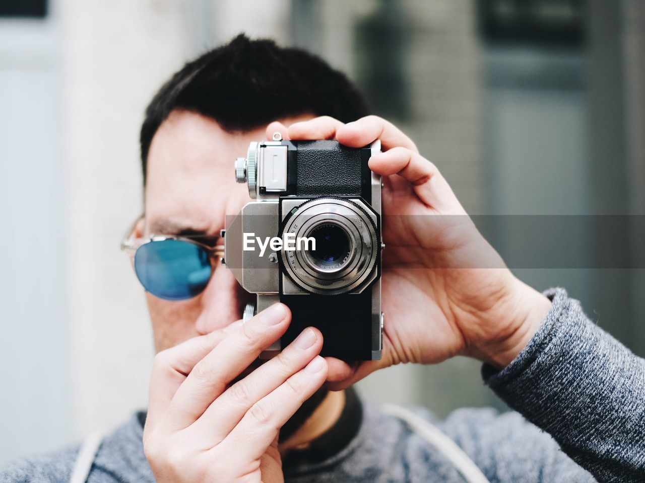camera - photographic equipment, photography themes, technology, photographing, one person, real people, holding, focus on foreground, photographic equipment, occupation, human hand, men, lifestyles, activity, leisure activity, hand, adult, casual clothing, portrait, photographer, digital camera, slr camera