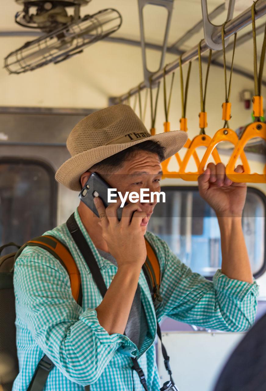 Man talking on mobile phone in bus