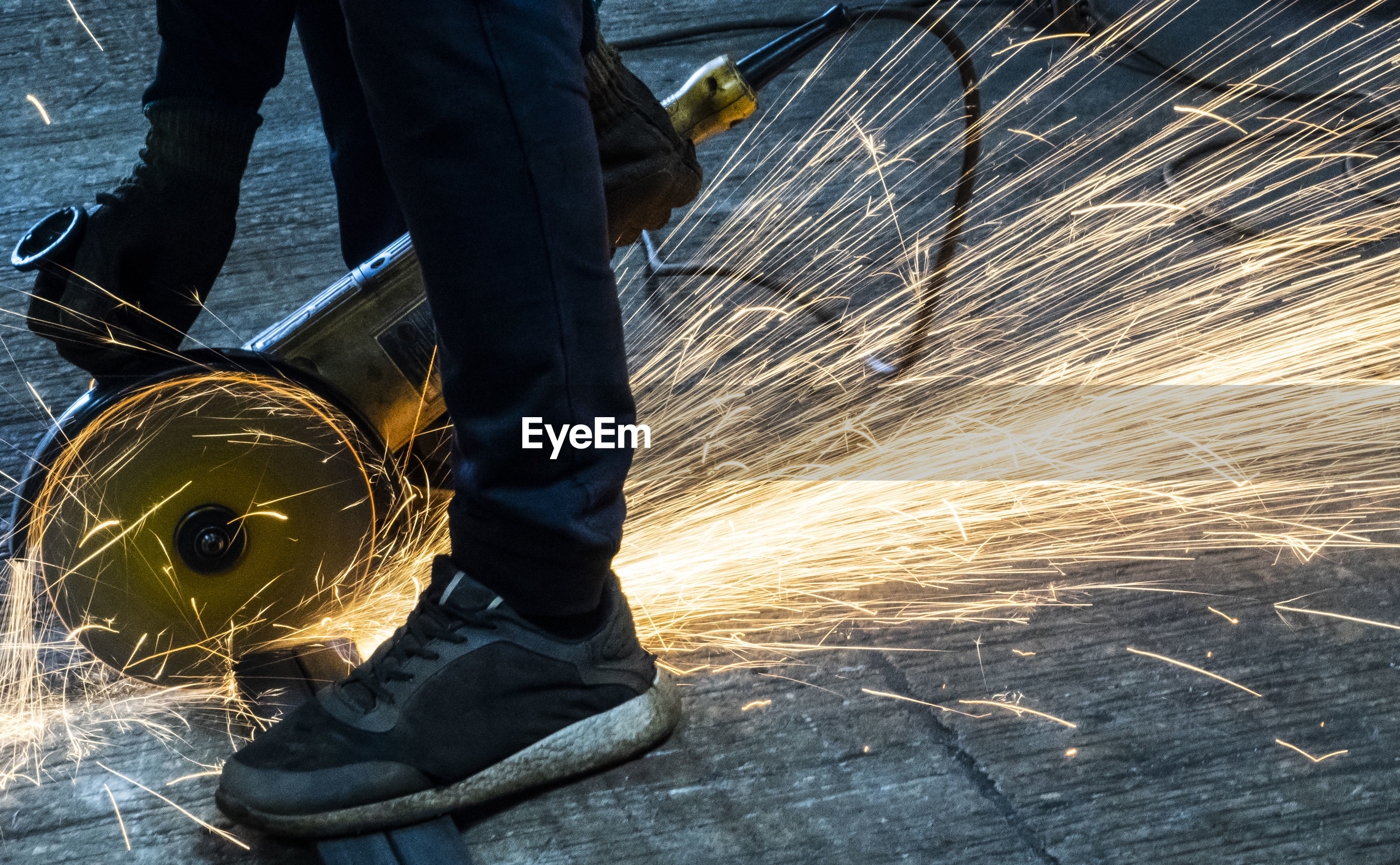Low section of man using grinder at workshop