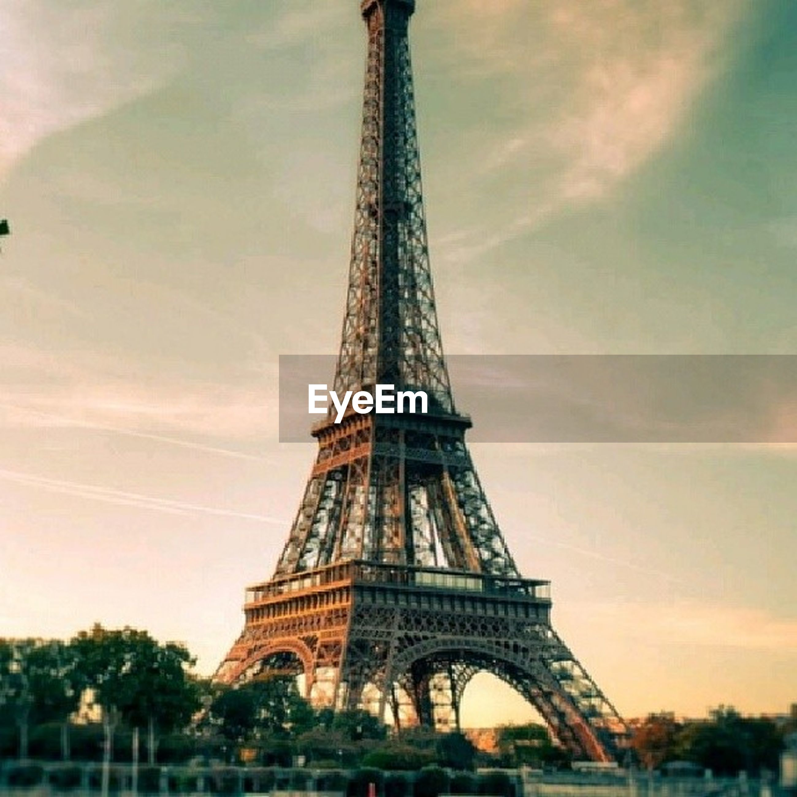 eiffel tower, architecture, famous place, international landmark, built structure, travel destinations, tourism, capital cities, sky, travel, tower, culture, tall - high, metal, history, low angle view, cloud - sky, architectural feature, city, tree