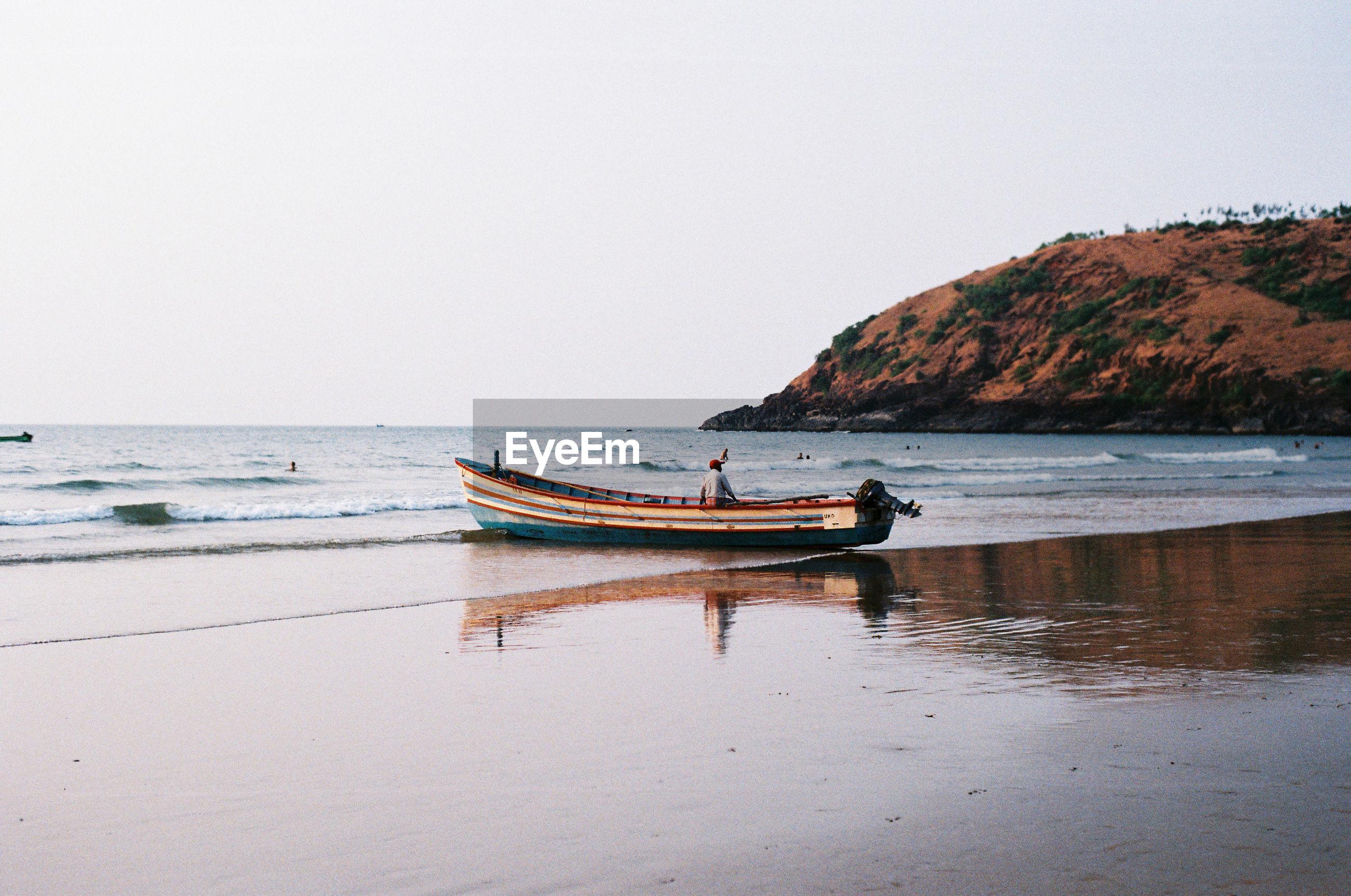 Man sitting in boat on beach