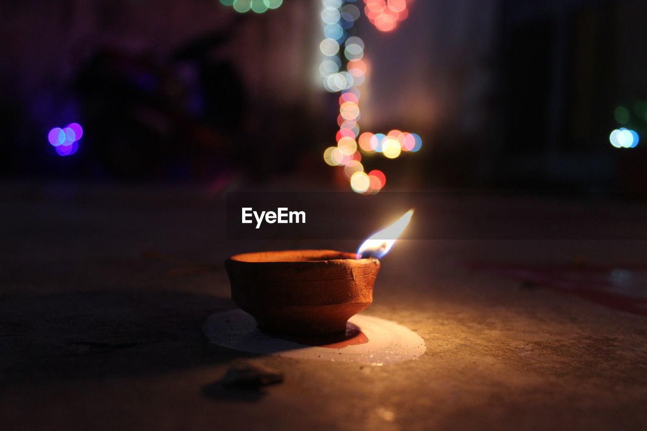 Close-Up Of Lit Diya Against Defocused Lights At Night