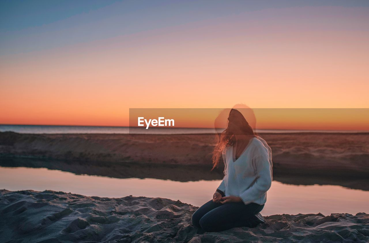 Multiple Image Of Woman Sitting On Rock By Sea Against Sky During Sunset