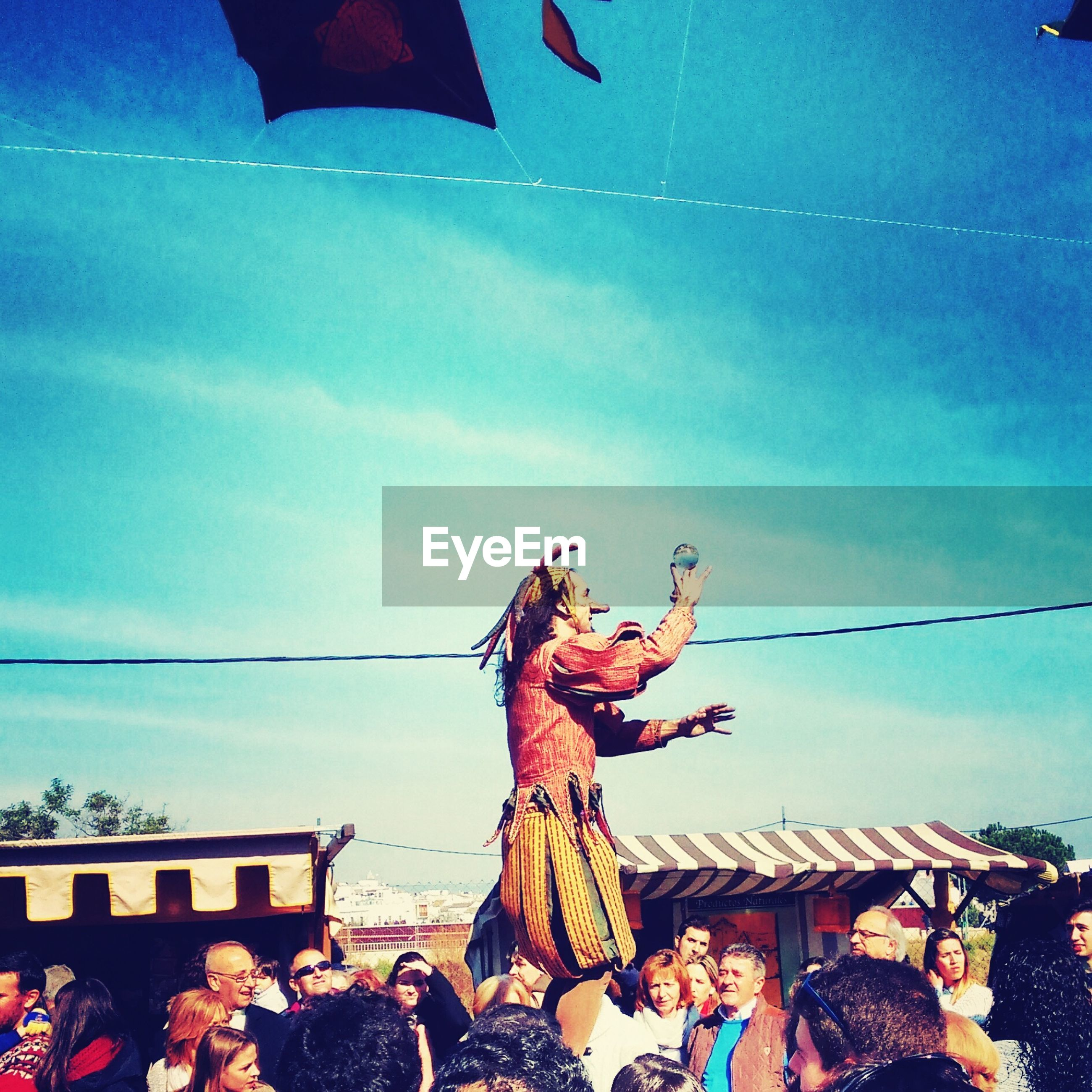 low angle view, sky, blue, arts culture and entertainment, outdoors, creativity, art and craft, no people, rope, art, day, animal representation, hanging, celebration, cloud - sky, cloud, fish, multi colored, nature, close-up