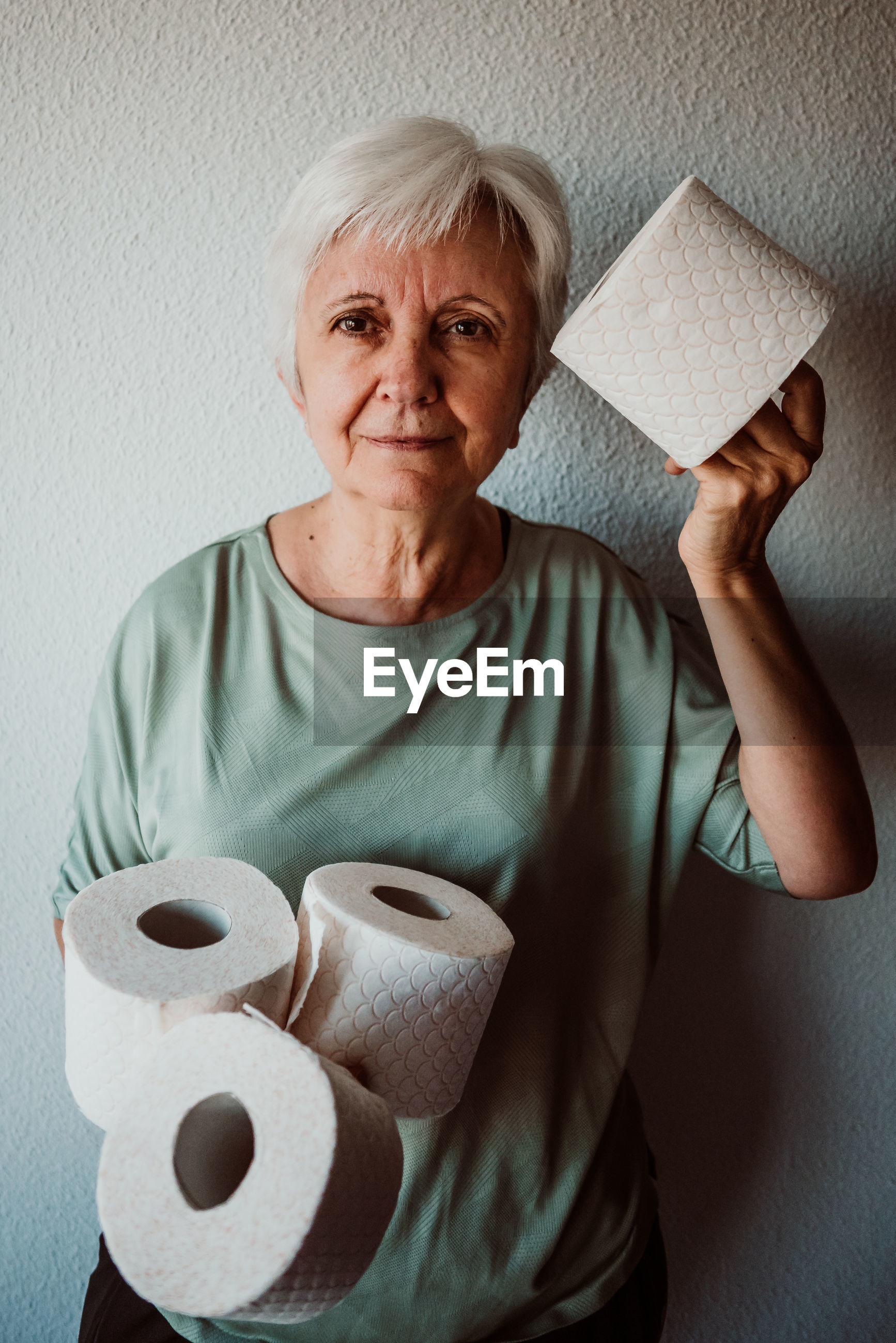 Sick senior woman holding tissue paper standing against wall