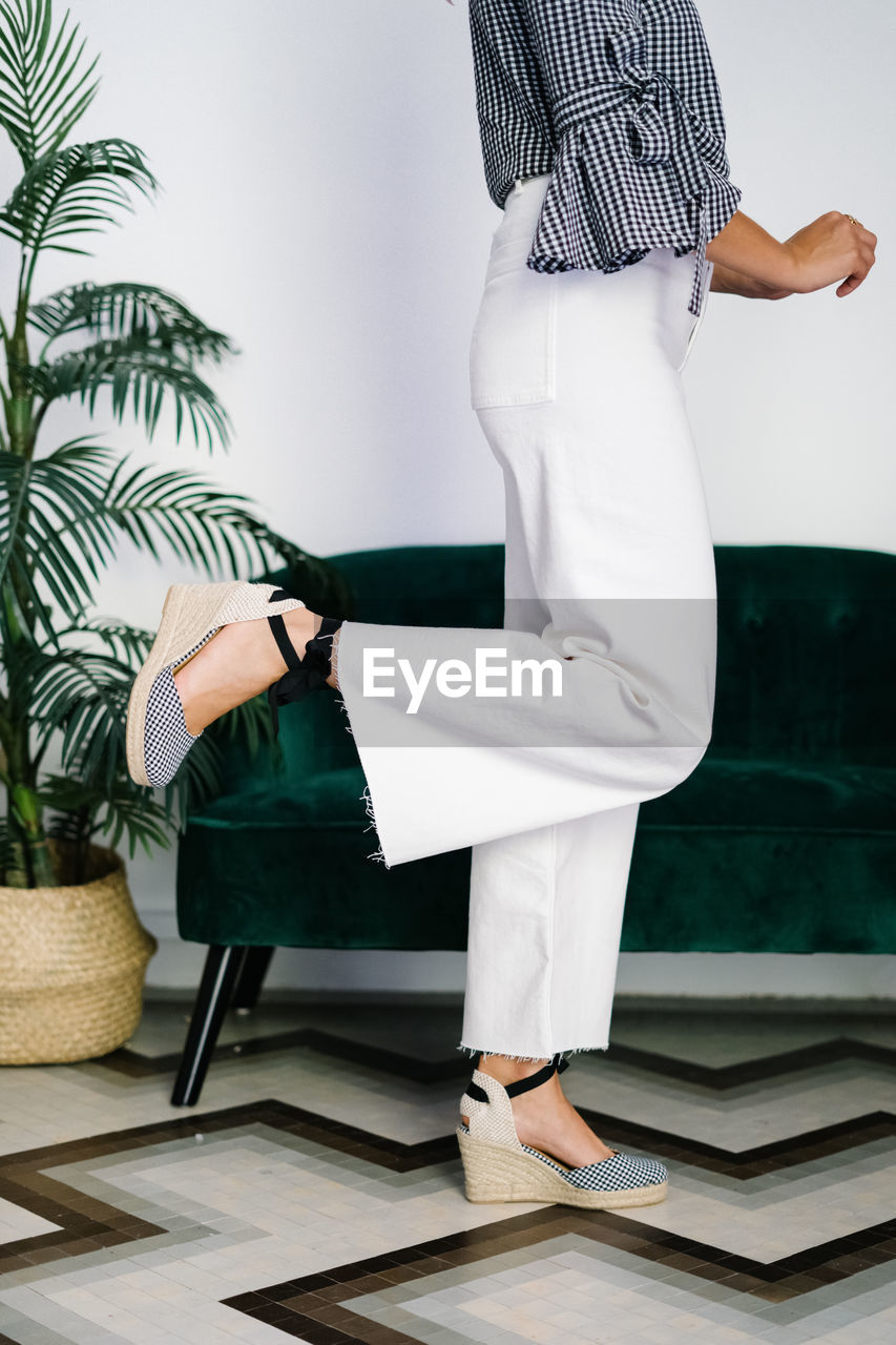 SIDE VIEW LOW SECTION OF WOMAN STANDING ON TABLE
