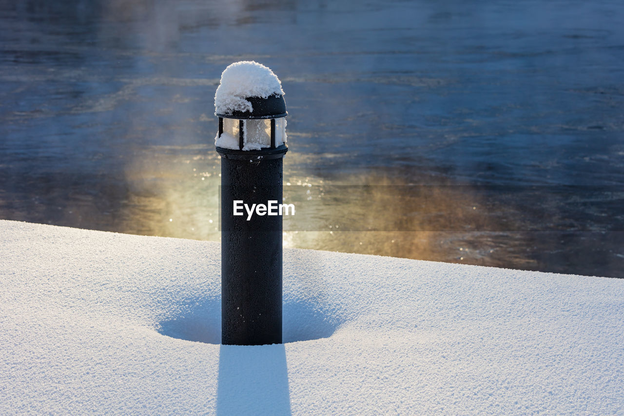 day, nature, cold temperature, no people, snow, winter, shadow, sunlight, water, outdoors, black color, post, close-up, white color, high angle view, lake, frozen, focus on foreground, pollution, melting