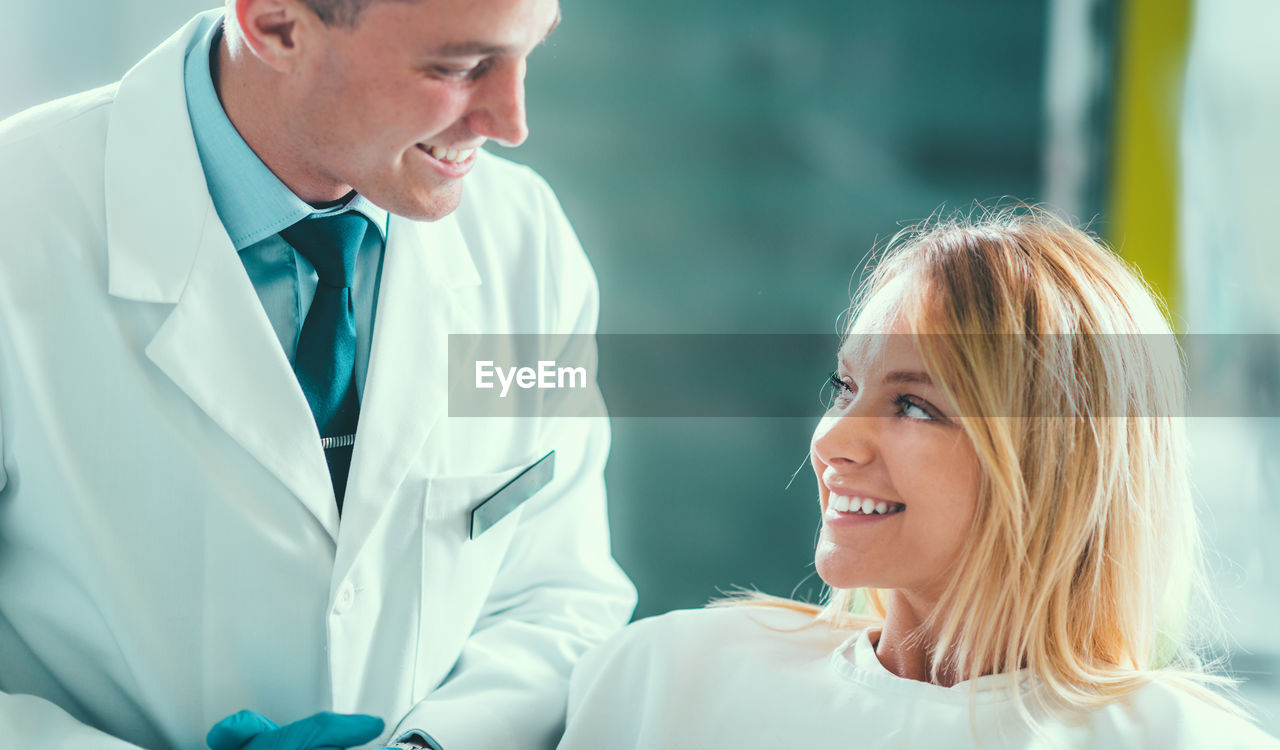 Smiling patient looking at dentist in clinic