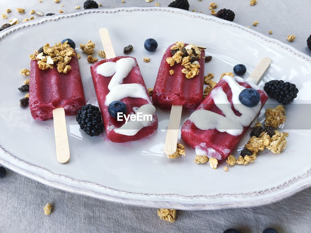 CLOSE-UP OF BERRY POPSICLES ON SERVING PLATE