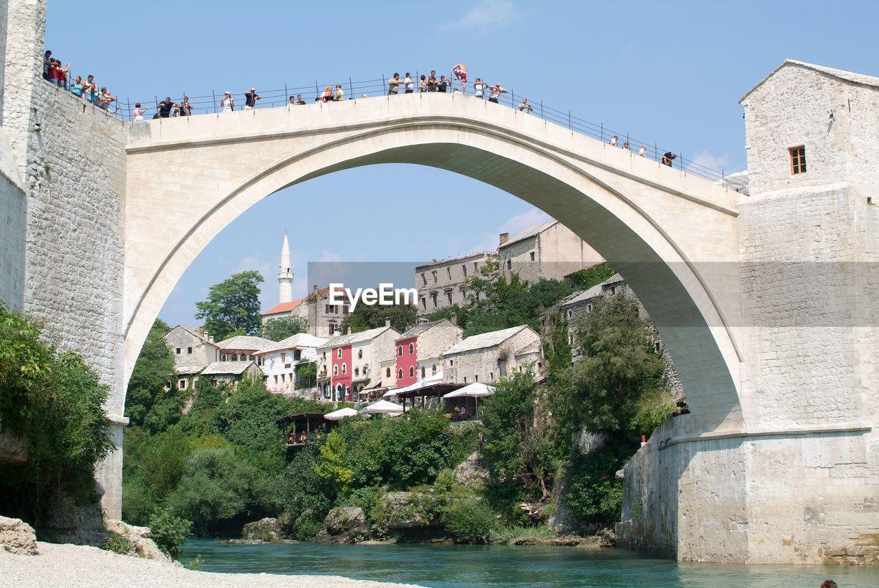 VIEW OF ARCH BRIDGE OVER RIVER AGAINST BUILDINGS
