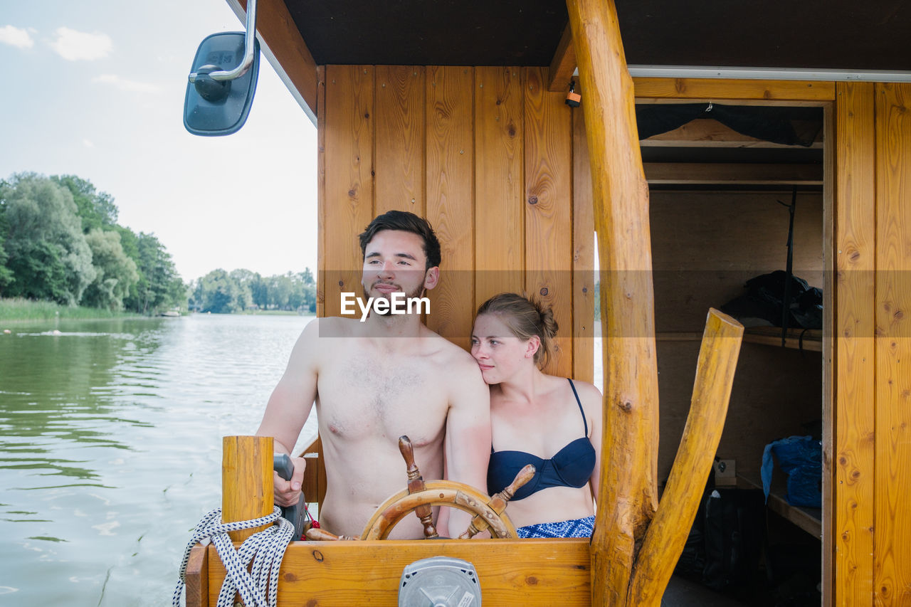 shirtless, men, real people, two people, water, leisure activity, portrait, lifestyles, males, togetherness, looking at camera, sitting, smiling, nautical vessel, day, wood - material, boys, nature, outdoors