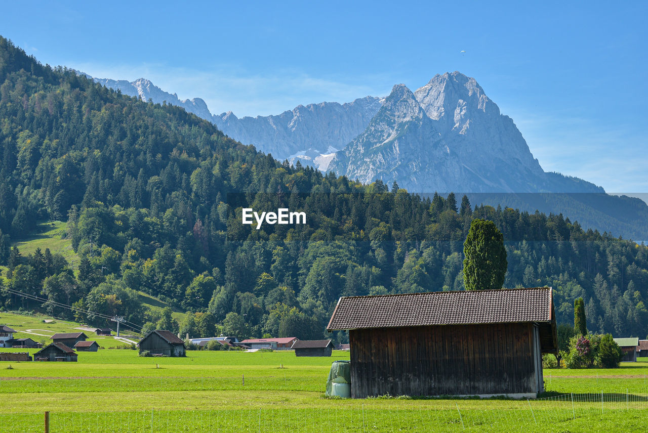 mountain, scenics - nature, beauty in nature, plant, landscape, tree, environment, land, field, architecture, built structure, sky, green color, tranquil scene, tranquility, grass, nature, non-urban scene, idyllic, rural scene, mountain range, no people, outdoors, cottage, mountain peak