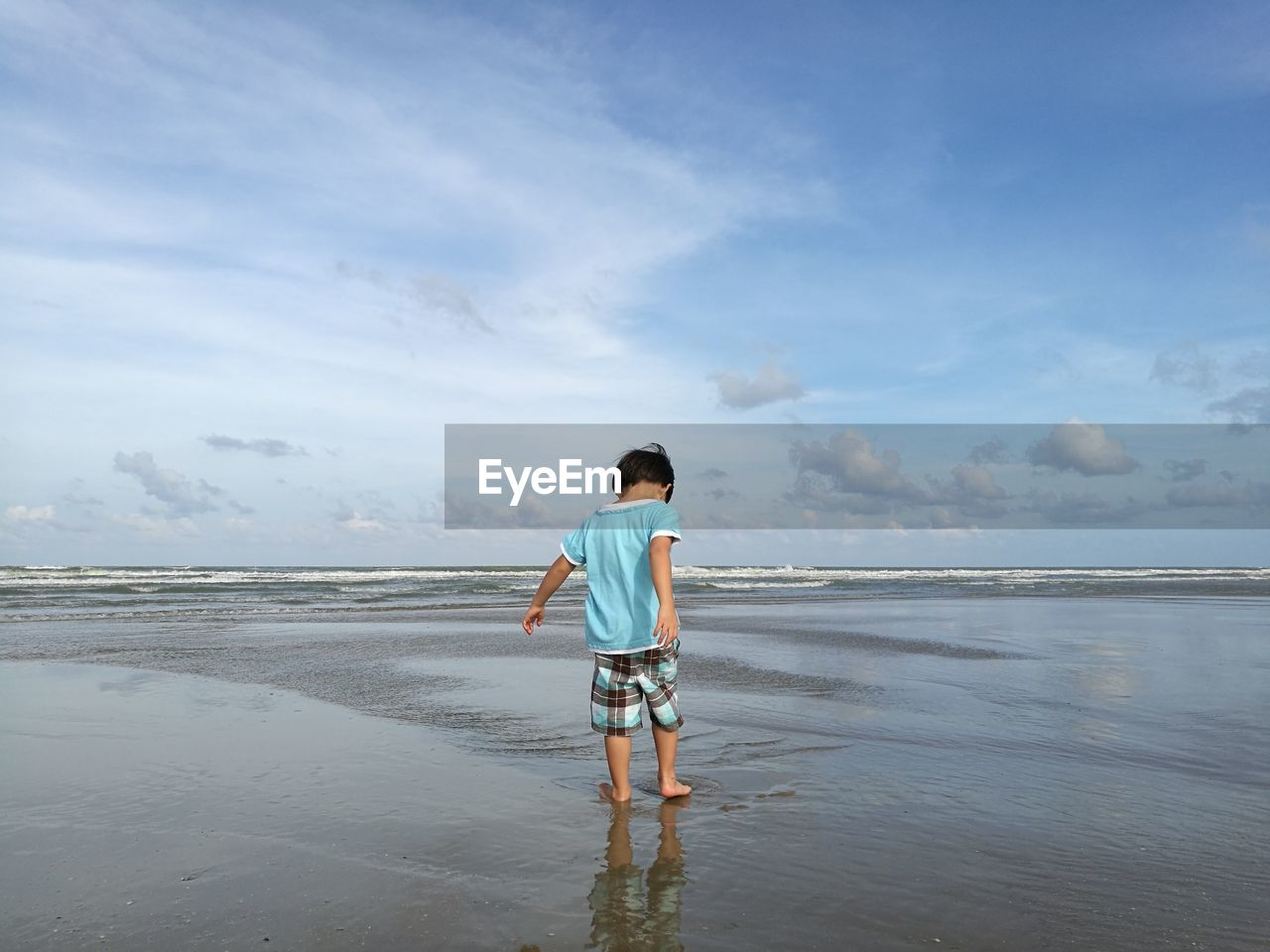 Rear view of boy standing on shore at beach against cloudy sky