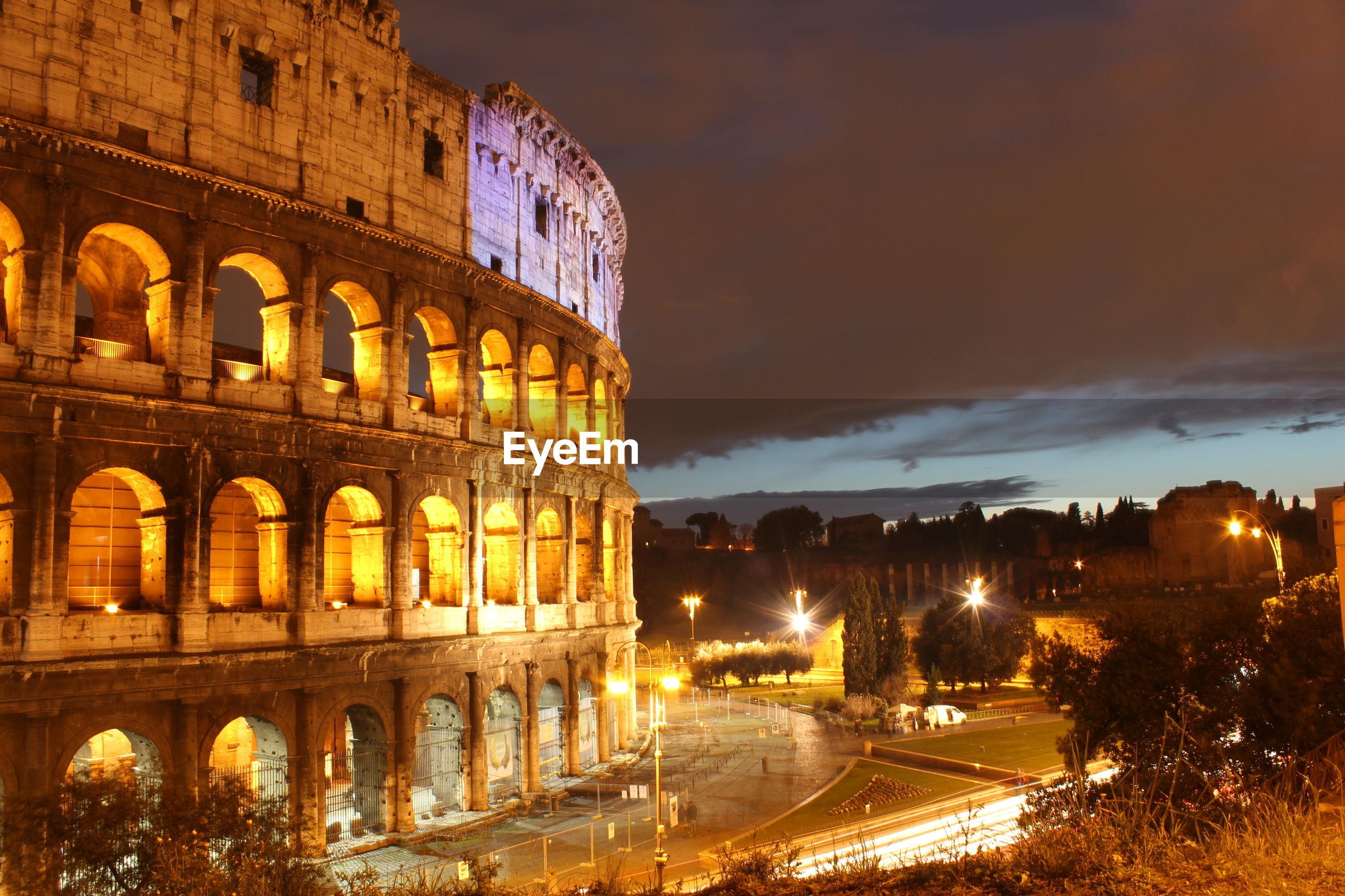 Illuminated coliseum against sky at dusk