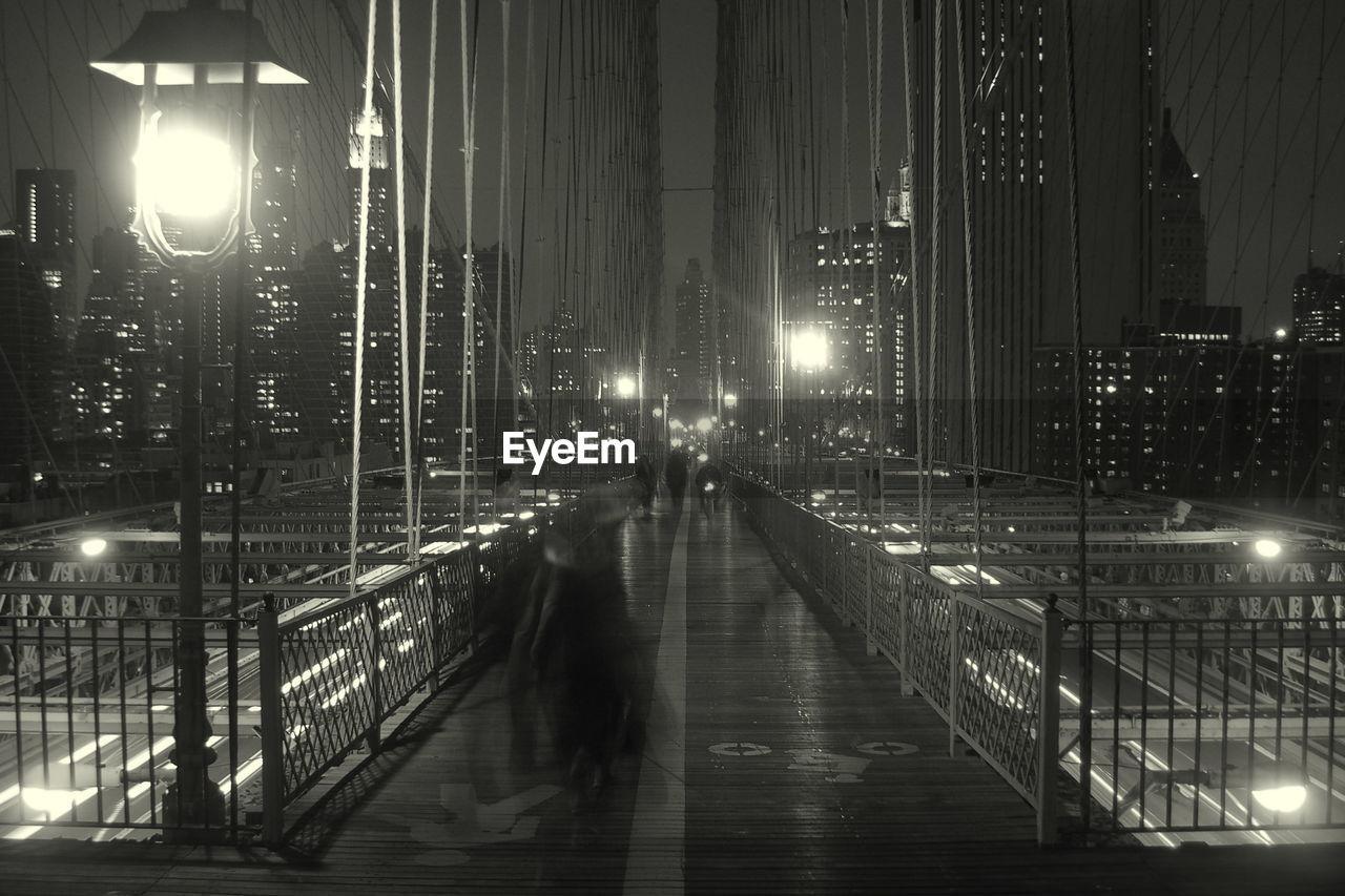 Illuminated Brooklyn Bridge Amidst Buildings At Night