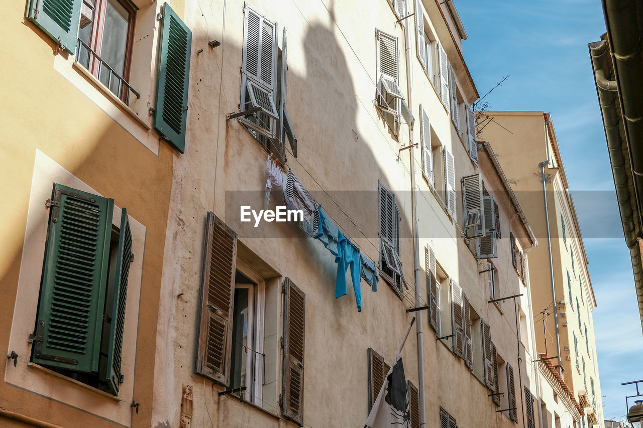 building exterior, architecture, built structure, window, building, low angle view, residential district, no people, day, outdoors, nature, city, lighting equipment, sky, drying, clothing, wall - building feature, sunlight, old, plant, apartment