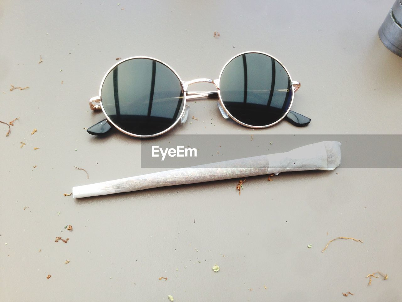 High Angle View Of Sunglasses With Marijuana Joint On Table
