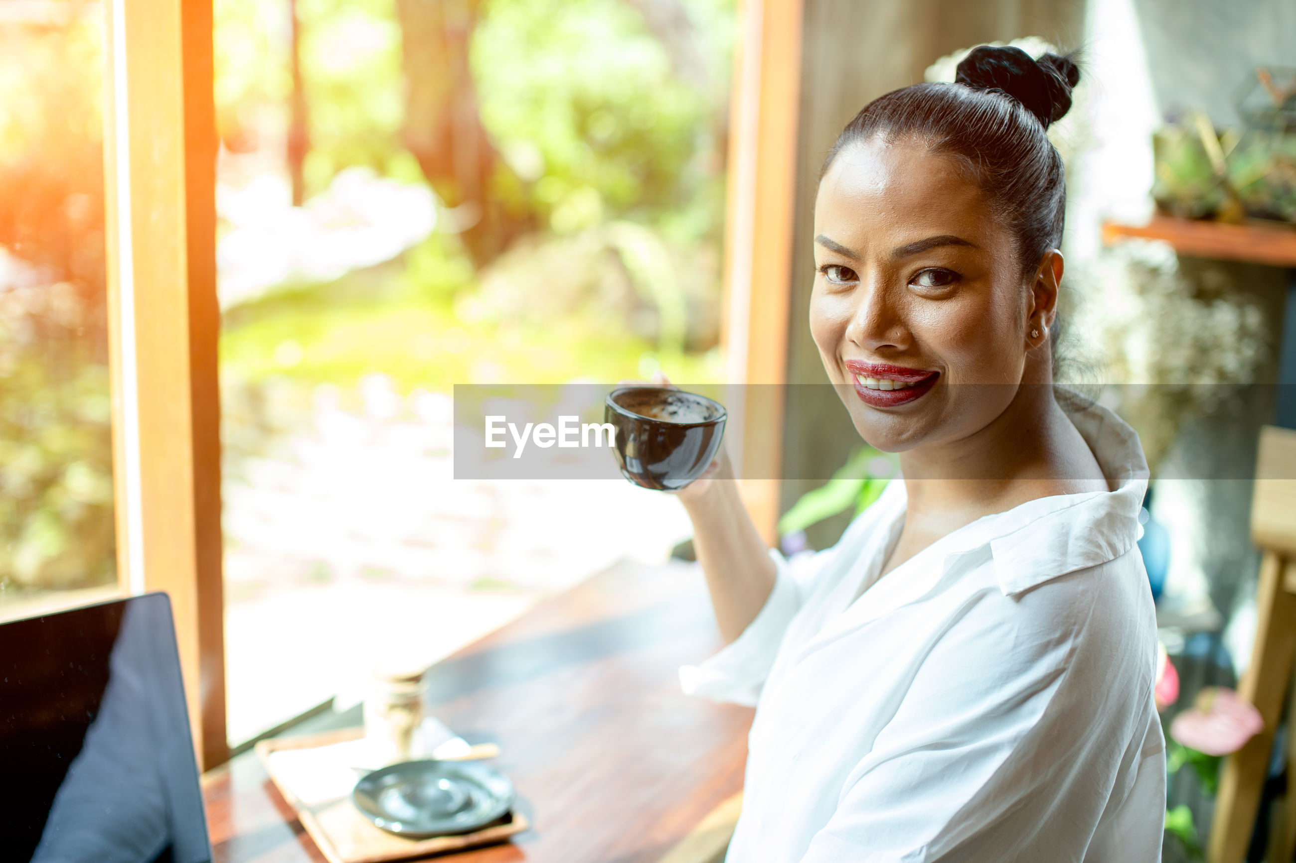 Portrait of smiling woman sitting in cafe