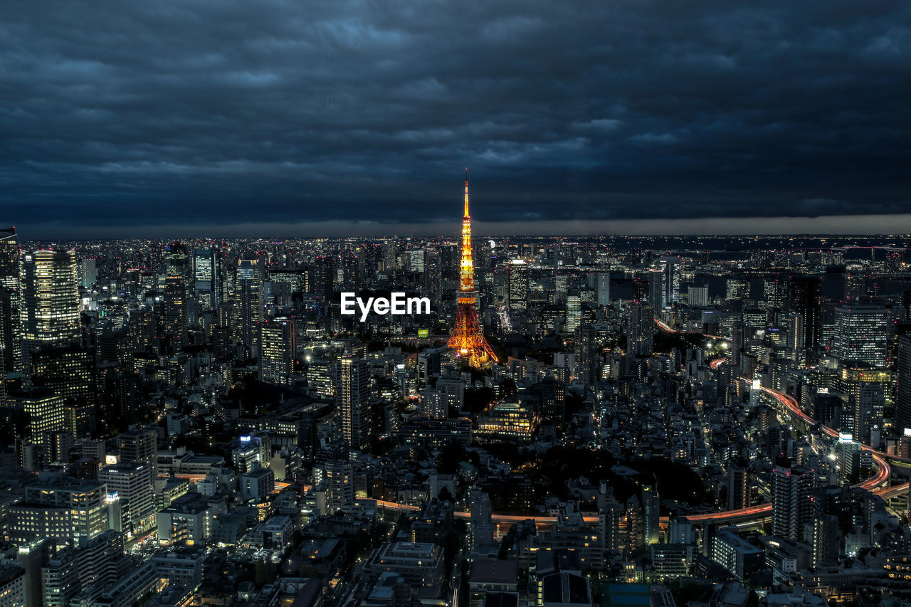 Aerial View Of Illuminated Tokyo Tower Amidst Buildings Against Cloudy Sky