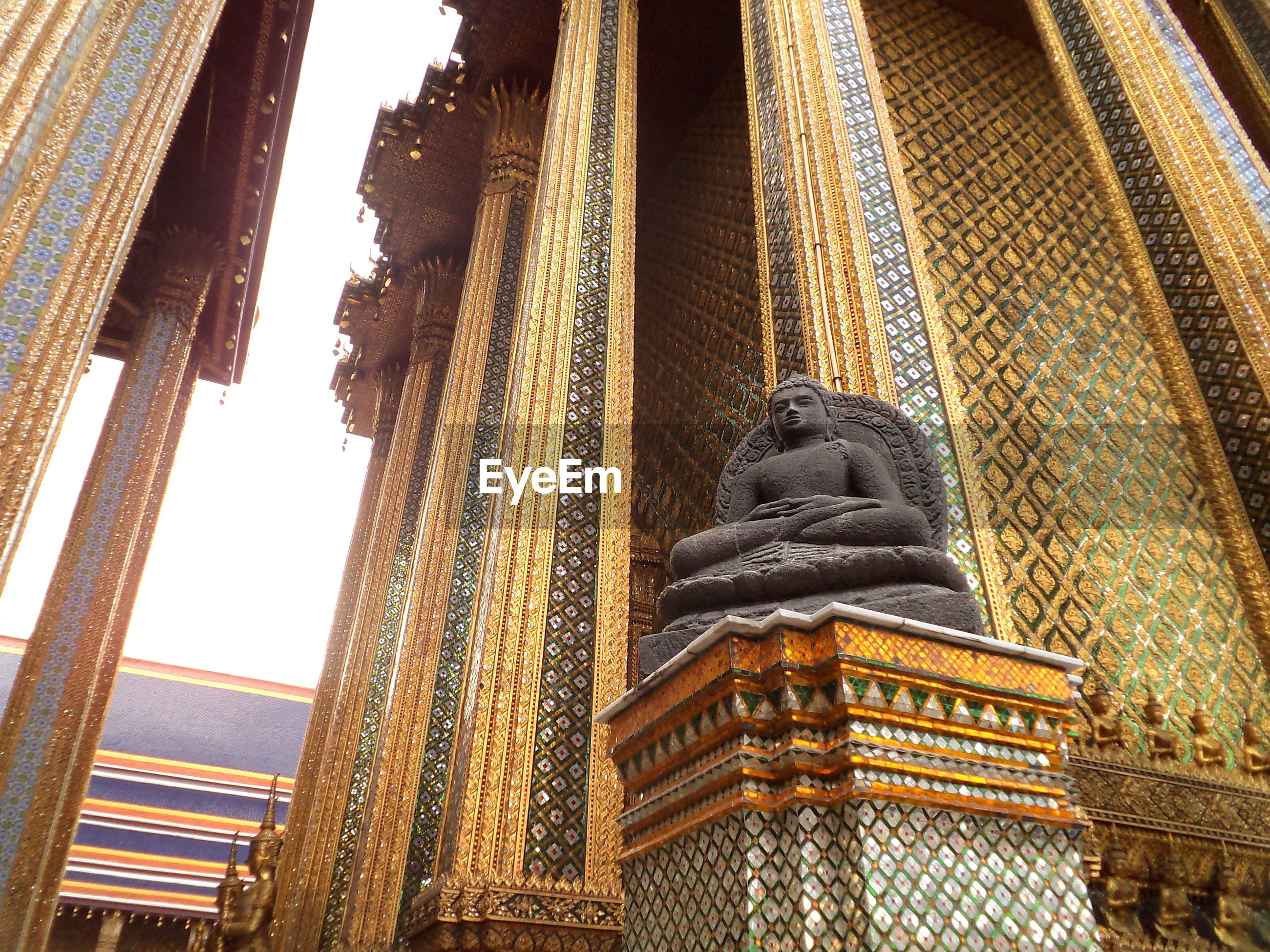 Low angle view of buddha statue at grand palace in city