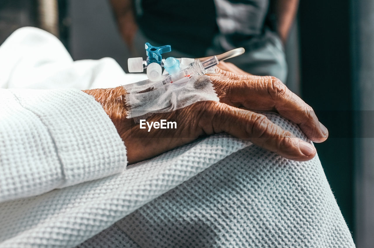 Close-up of medical equipment on wrinkled hand at hospital
