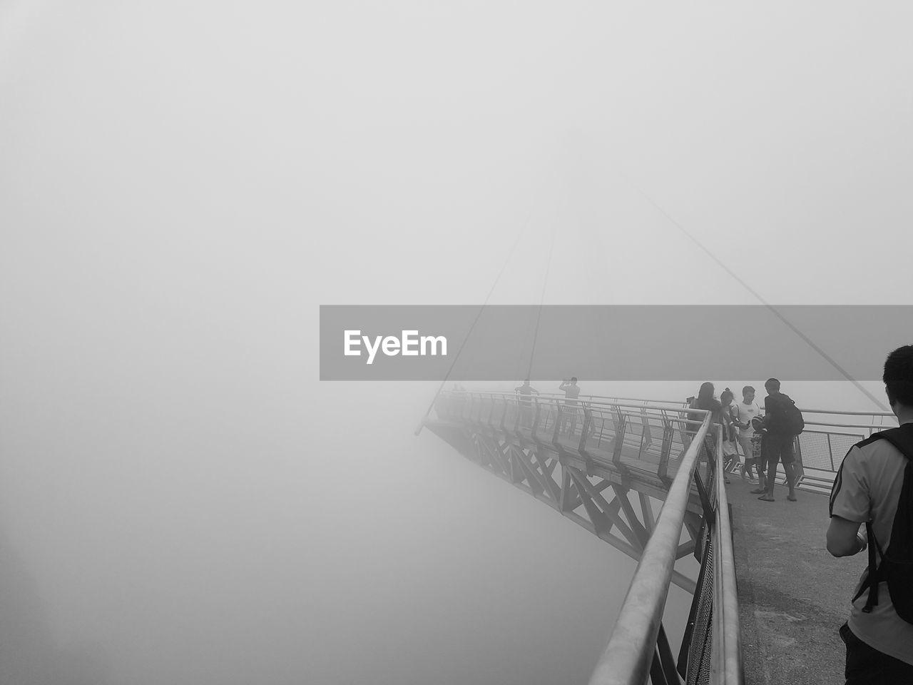 PEOPLE AT BRIDGE AGAINST SKY