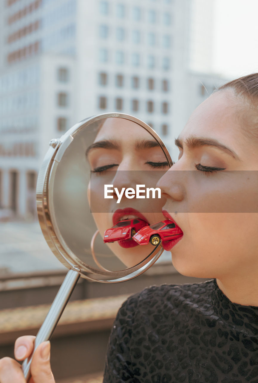 Close-up of young woman with red toy car in mouth while holding mirror with reflection in city