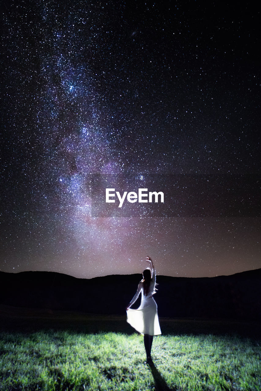 Woman walking on field against sky at night