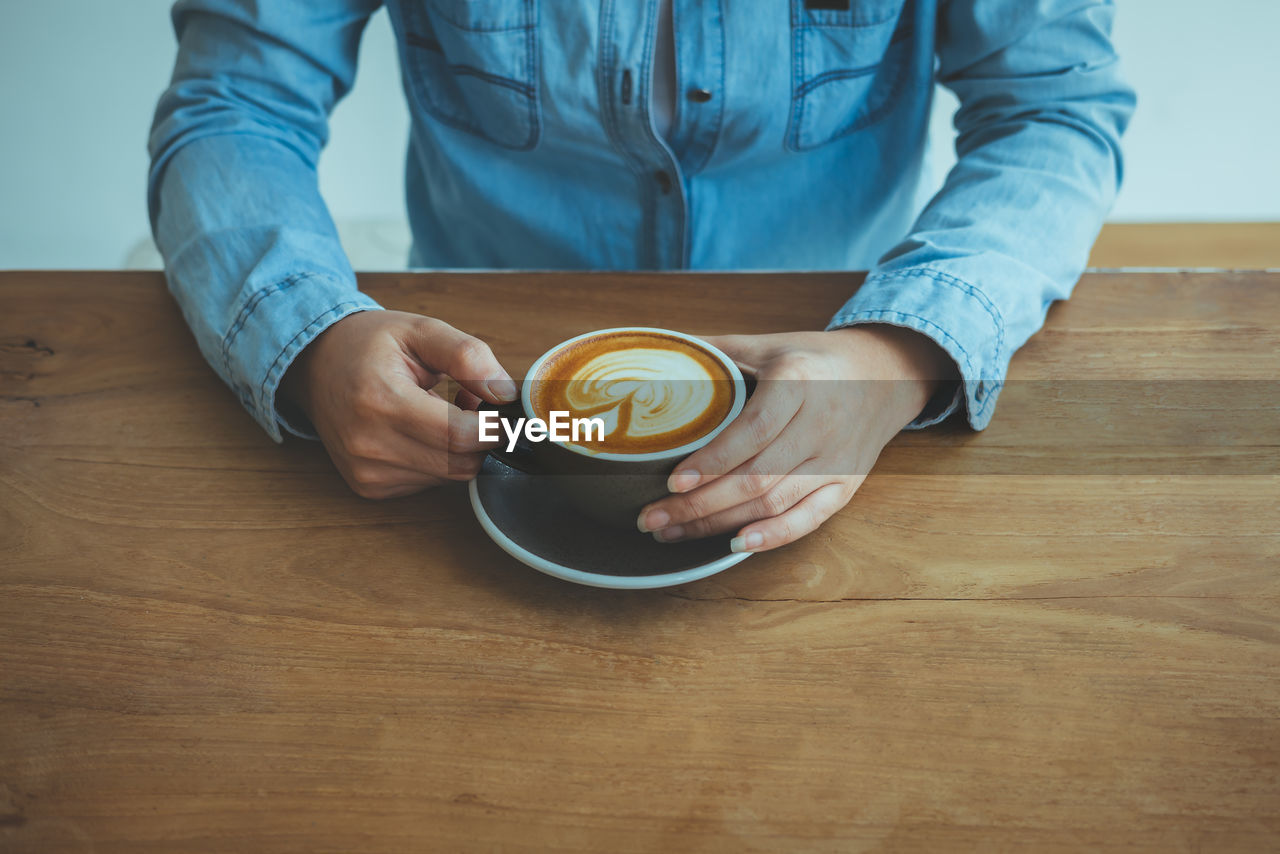 Midsection of man having coffee at table