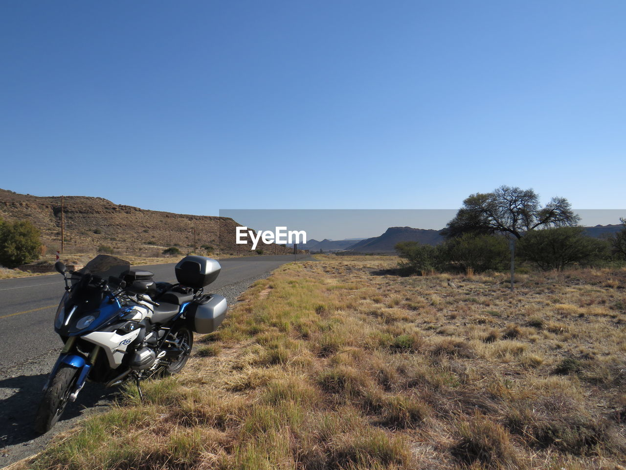 MOTORCYCLE ON FIELD AGAINST CLEAR SKY