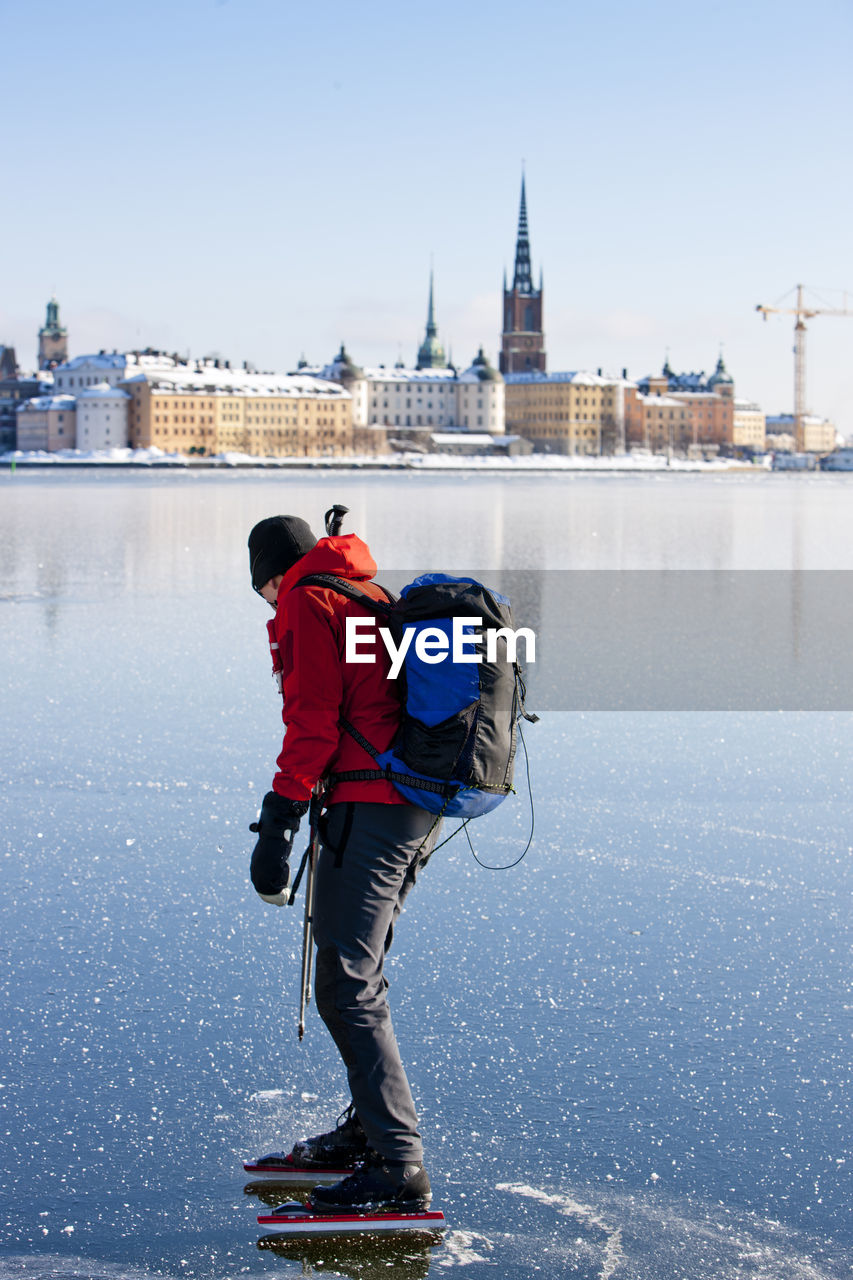 FULL LENGTH REAR VIEW OF MAN IN CITY DURING WINTER