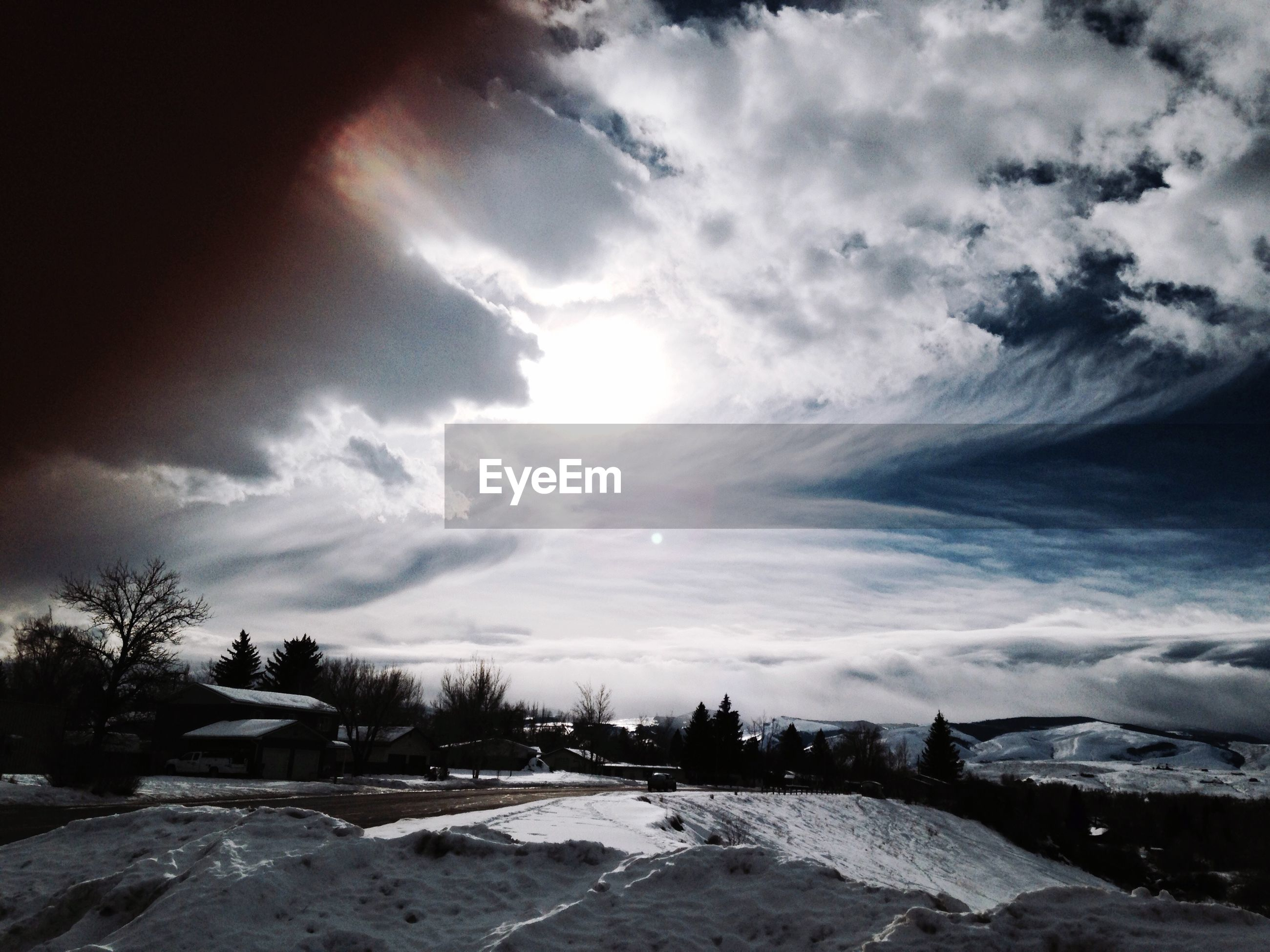 Houses and trees on snow covered mountain against cloudy sky