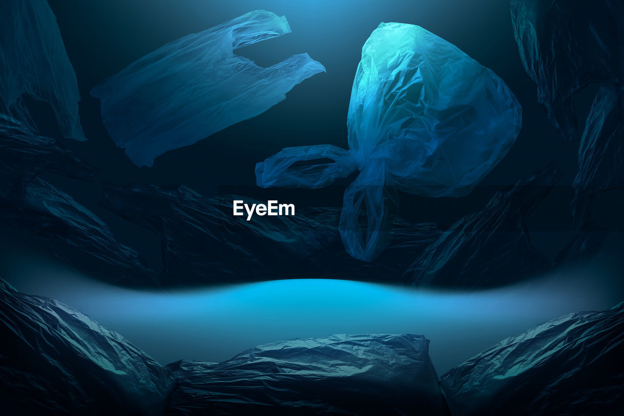 Creative background of single-use plastic bags floating in deep blue sea or ocean
