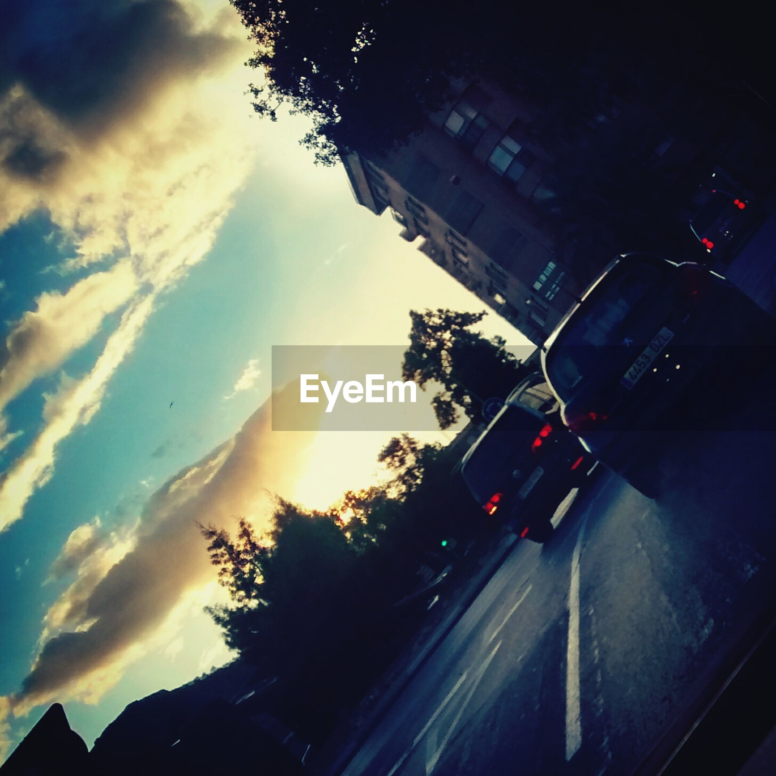 transportation, car, land vehicle, mode of transport, sky, tree, sunset, road, street, cloud - sky, silhouette, building exterior, built structure, travel, architecture, traffic, on the move, city, cloud, outdoors
