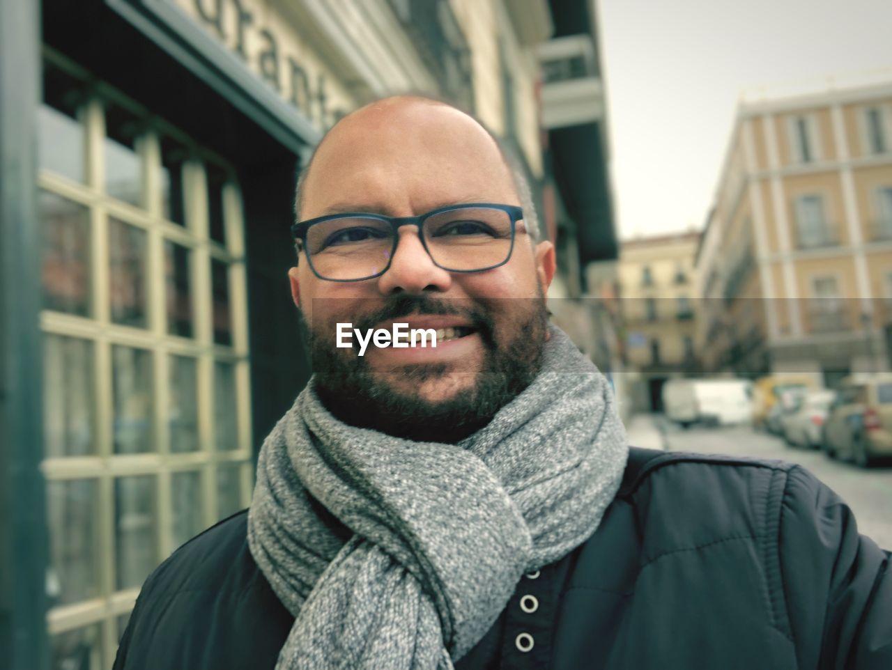 Portrait of man wearing eyeglasses in city during winter