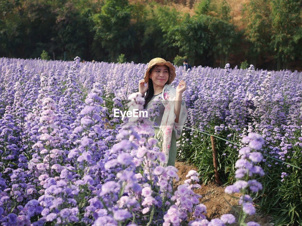 Portrait of woman with purple flowers on plants