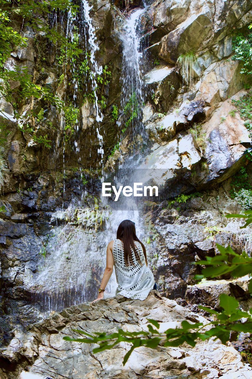 Rear view of woman looking at waterfall while sitting on rock