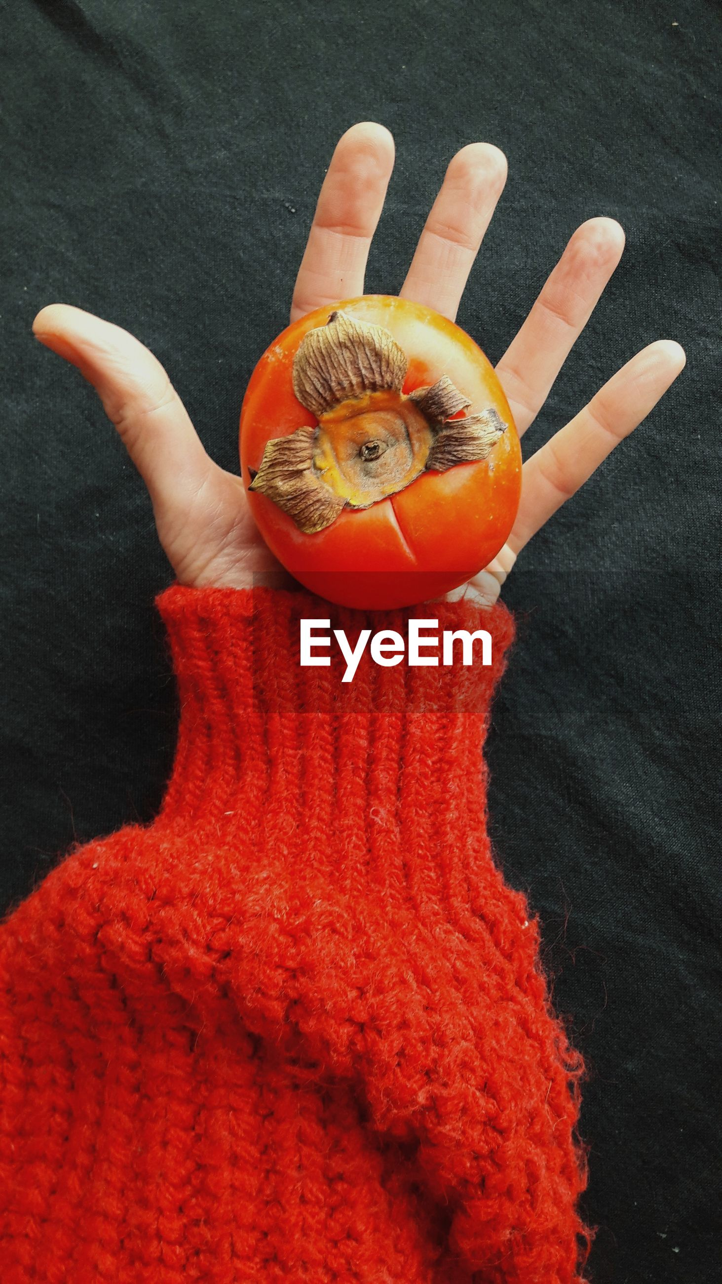 HIGH ANGLE VIEW OF PERSON HAND HOLDING ORANGE