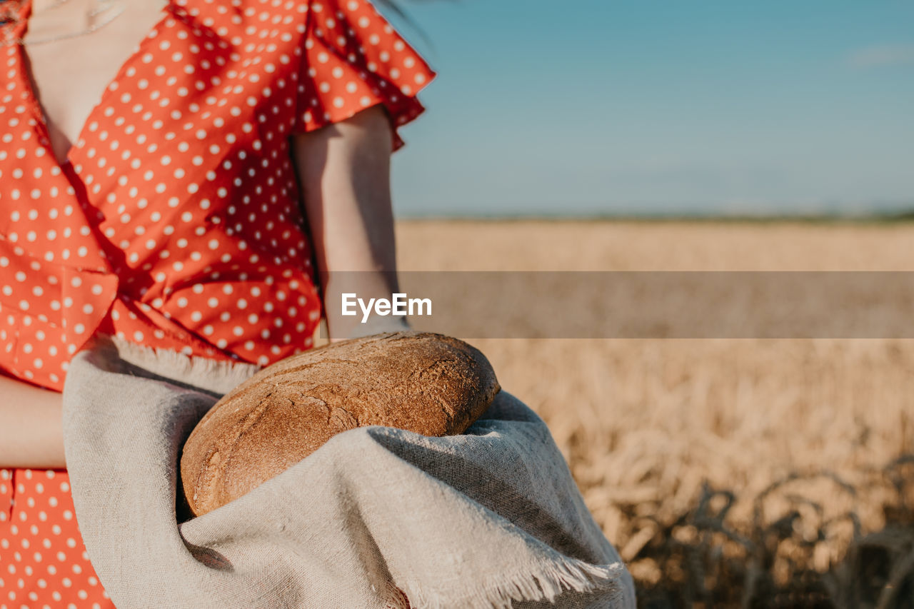Midsection of woman standing in field