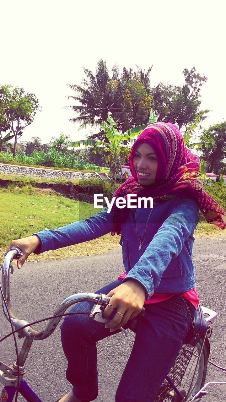 Woman with headscarf riding bicycle on road