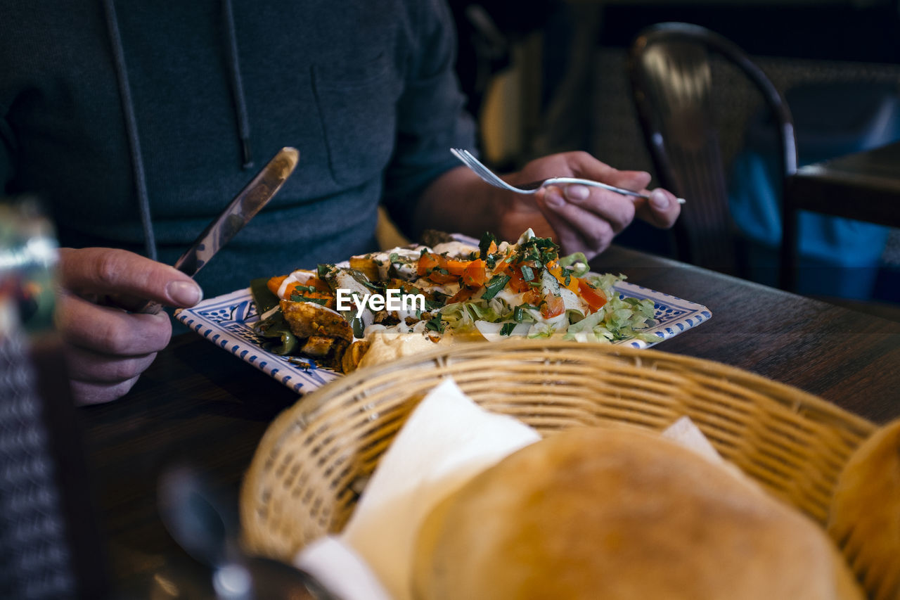 Midsection Of Man Heaving Meal At Table