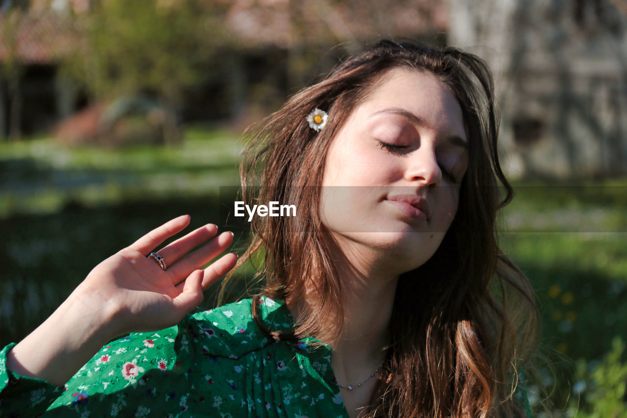 Young woman with closed eyes outdoors