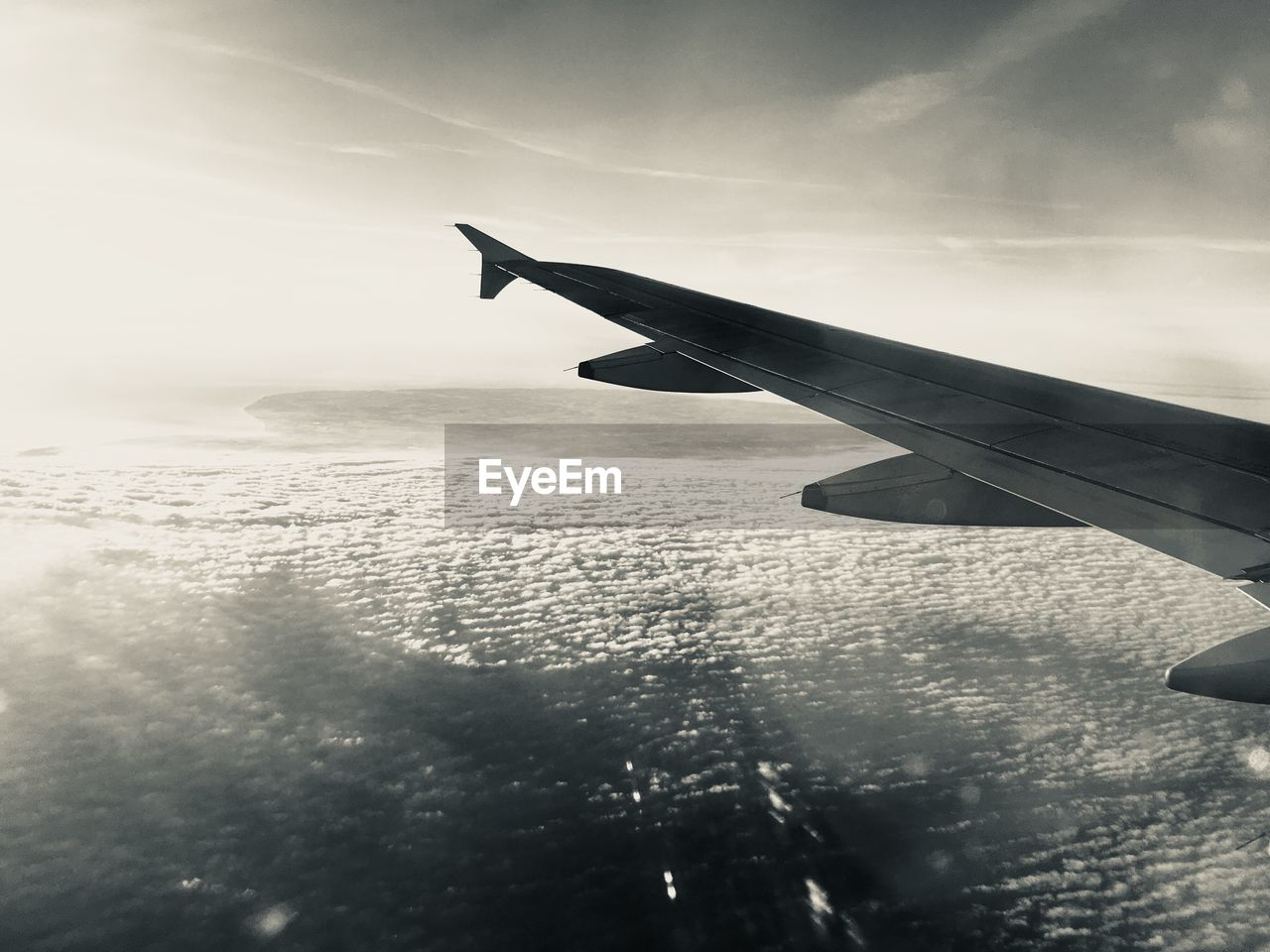 Cropped Image Airplane Wing Flying Over Sea Against Sky