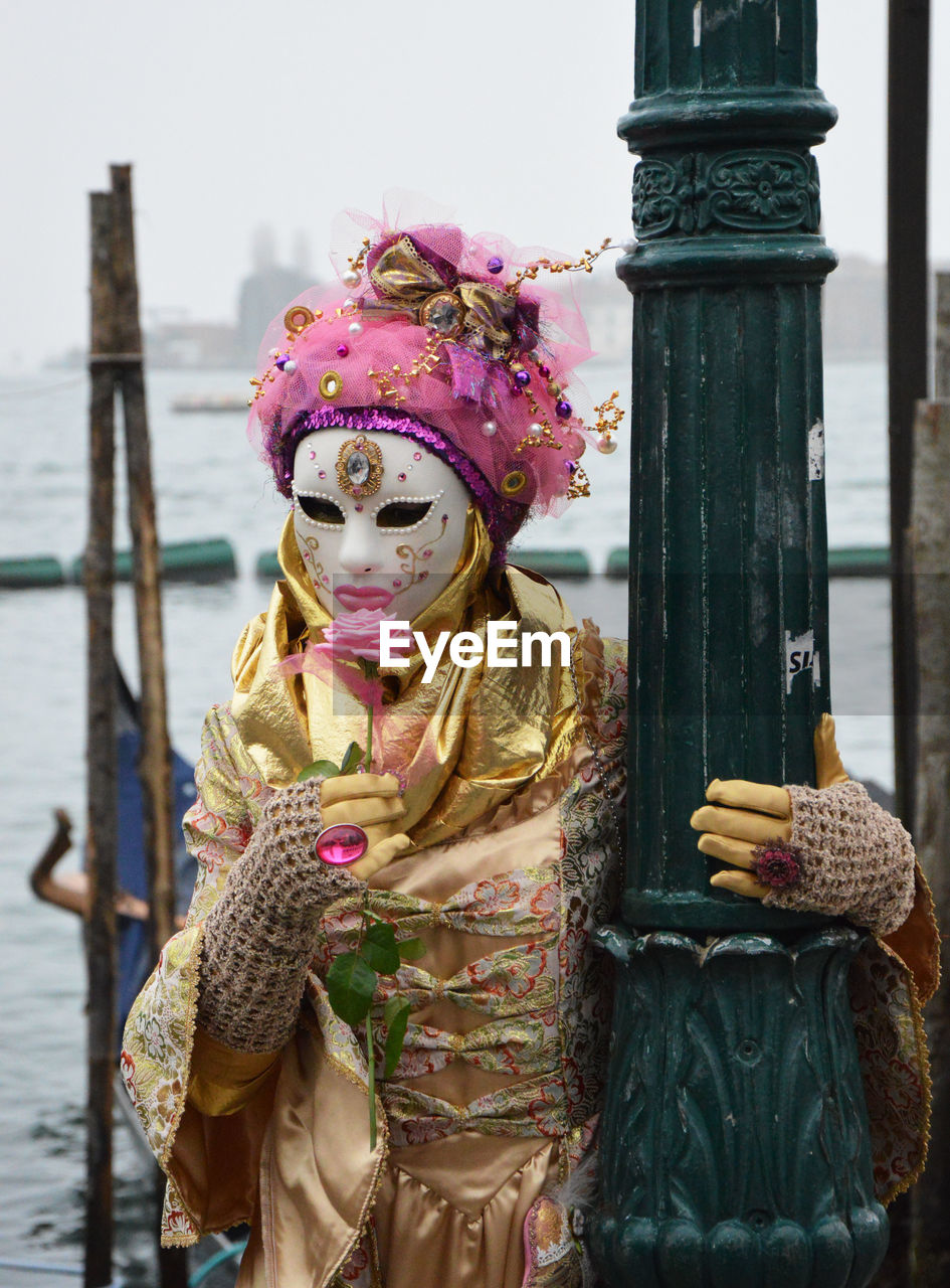 mask - disguise, female likeness, venetian mask, human representation, cultures, outdoors, focus on foreground, day, tradition, real people, one person, statue, water, close-up