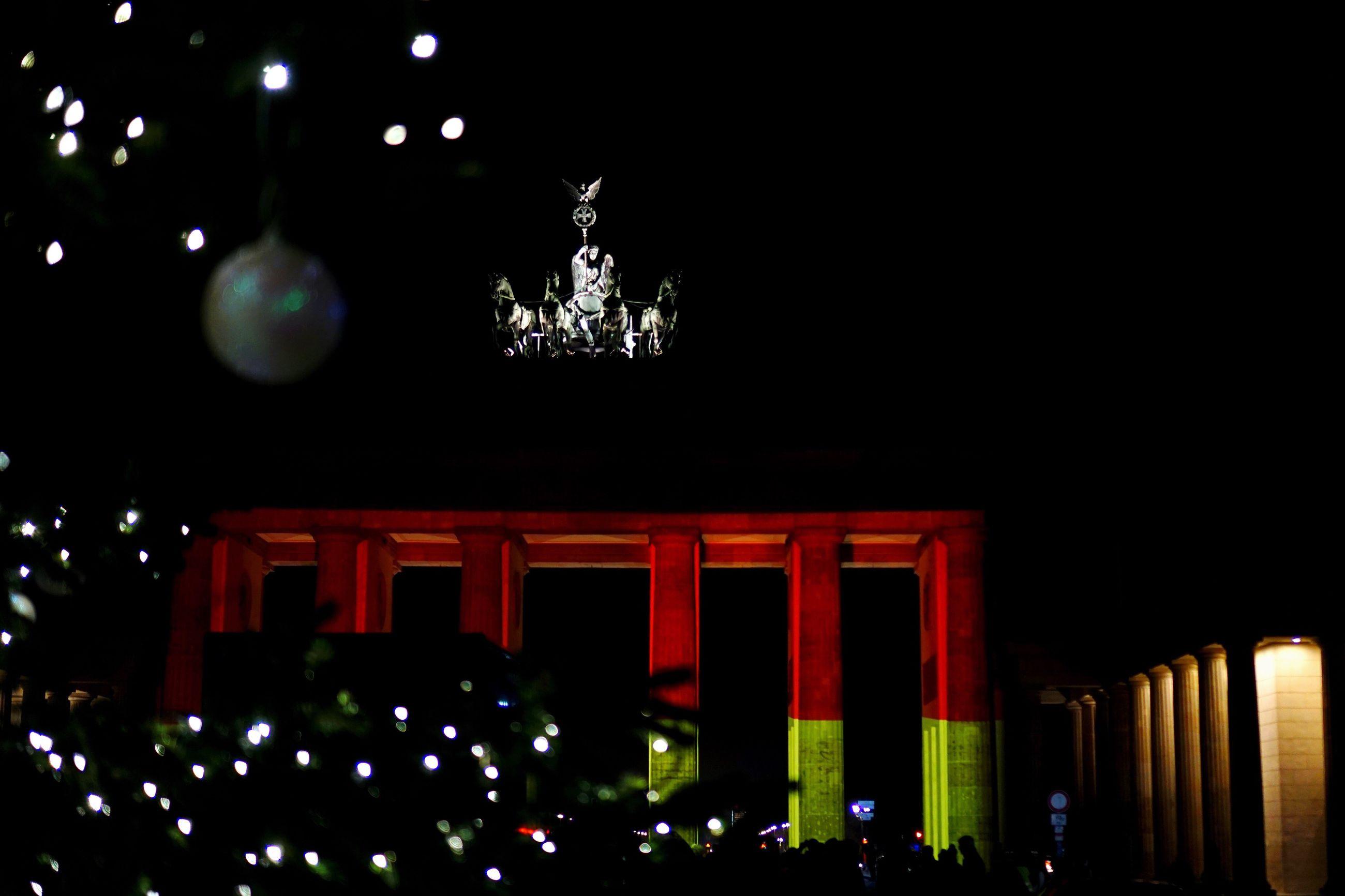Illuminated christmas lighting decoration at brandenburg gate during night