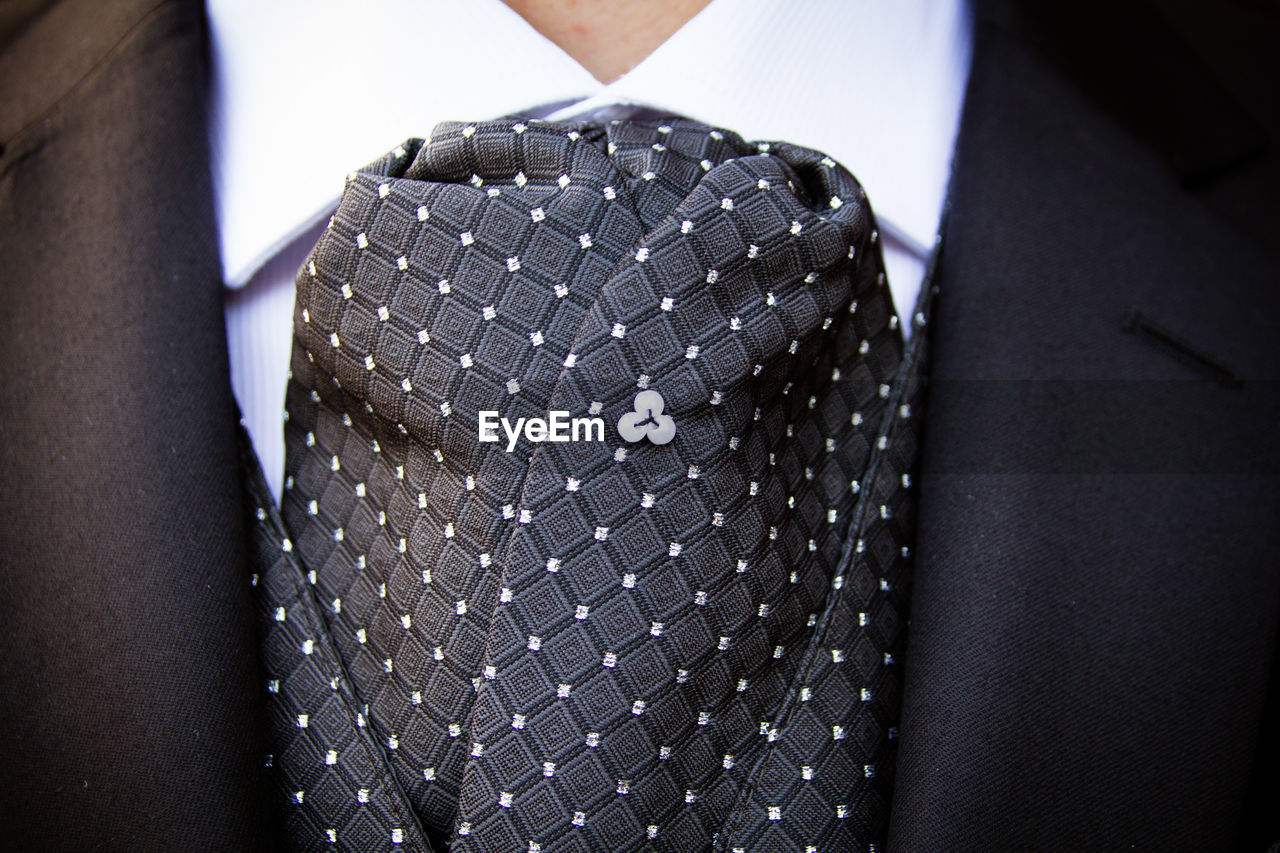 midsection, clothing, pattern, fashion, real people, focus on foreground, close-up, menswear, one person, necktie, well-dressed, suit, indoors, button down shirt, business, lifestyles, men, black color, personal accessory