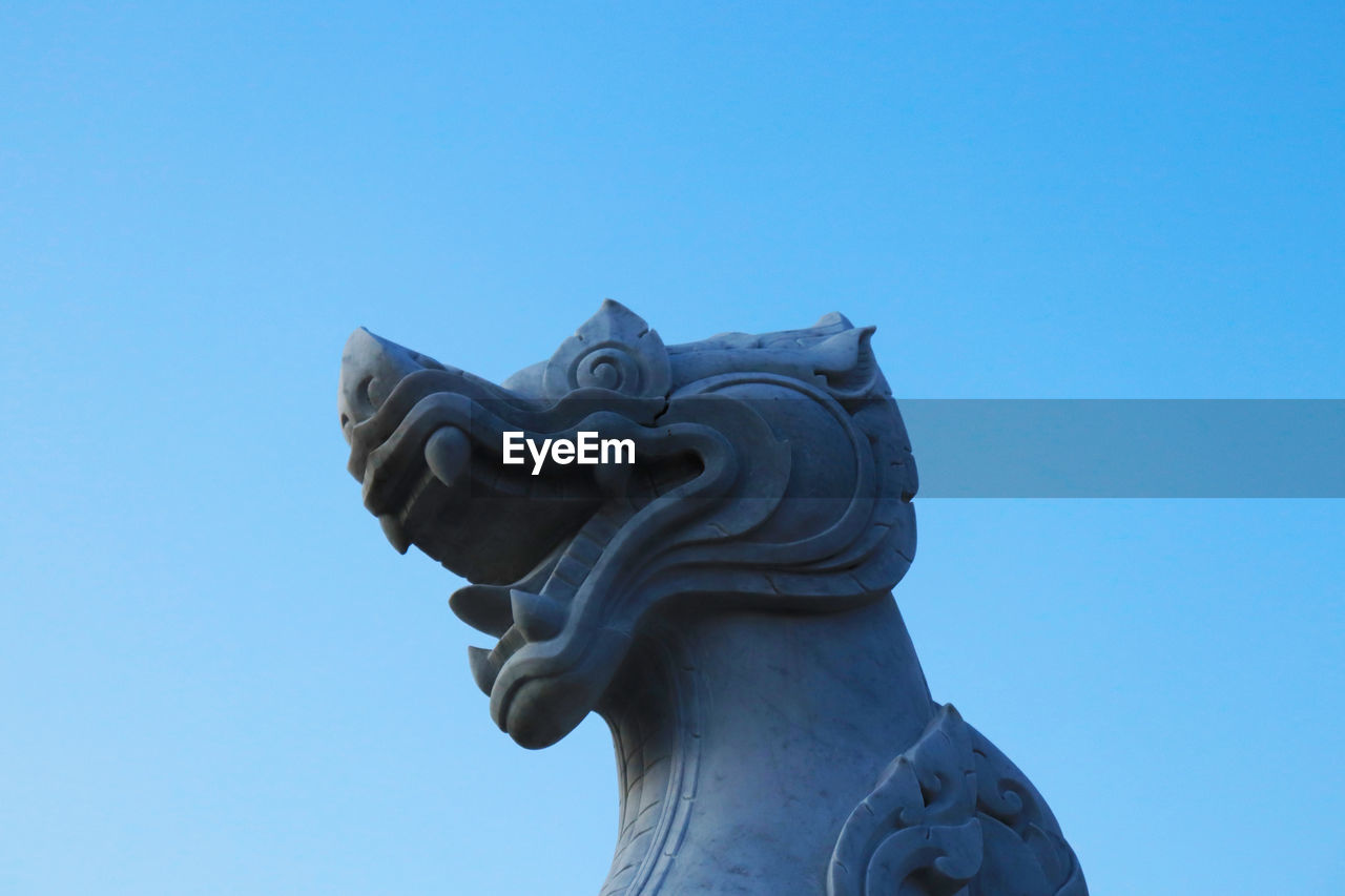 creativity, art and craft, sky, sculpture, representation, copy space, clear sky, statue, low angle view, blue, craft, animal representation, no people, nature, day, religion, architecture, belief, spirituality, carving - craft product, ornate